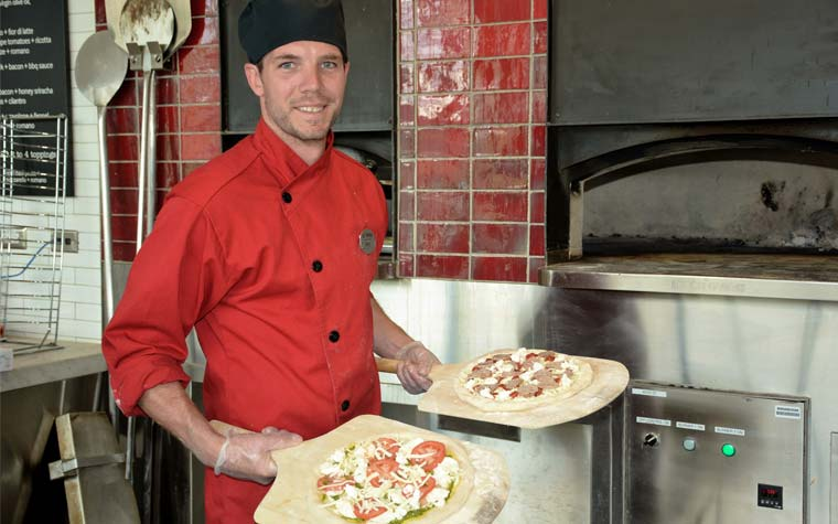 Kyle Rosch in front of pizza oven